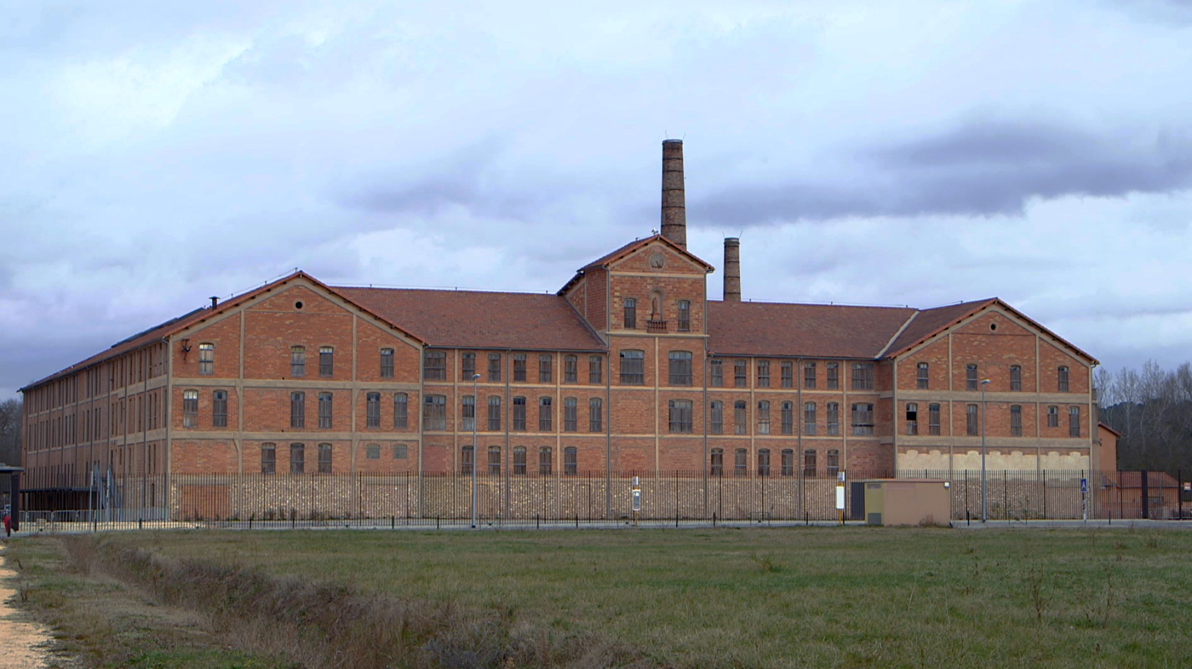 Grande usine en briques avec ciel couvert