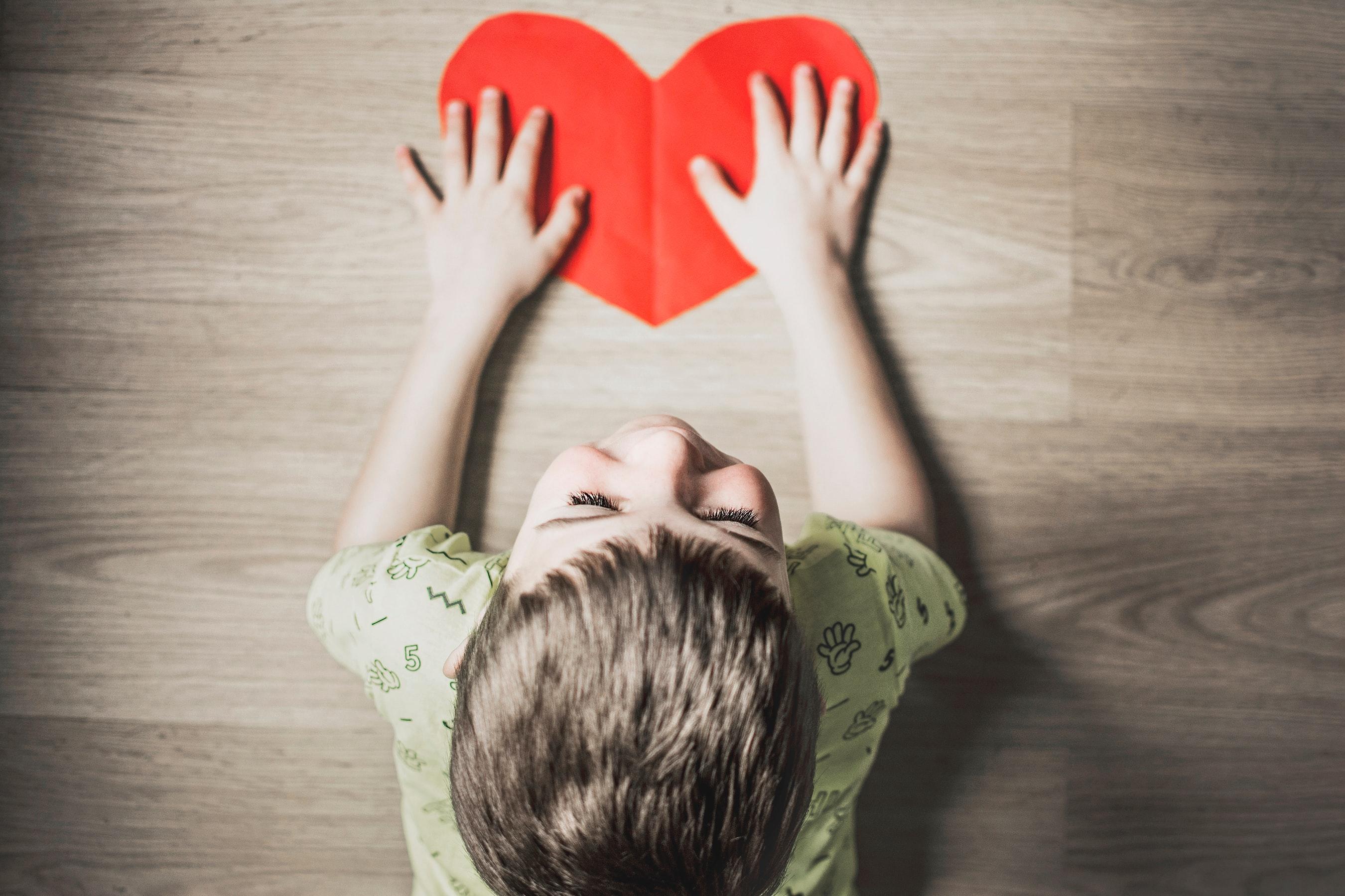 Photo d'un enfant avec un coeur (pas un vrai, un en papier) dans les mains