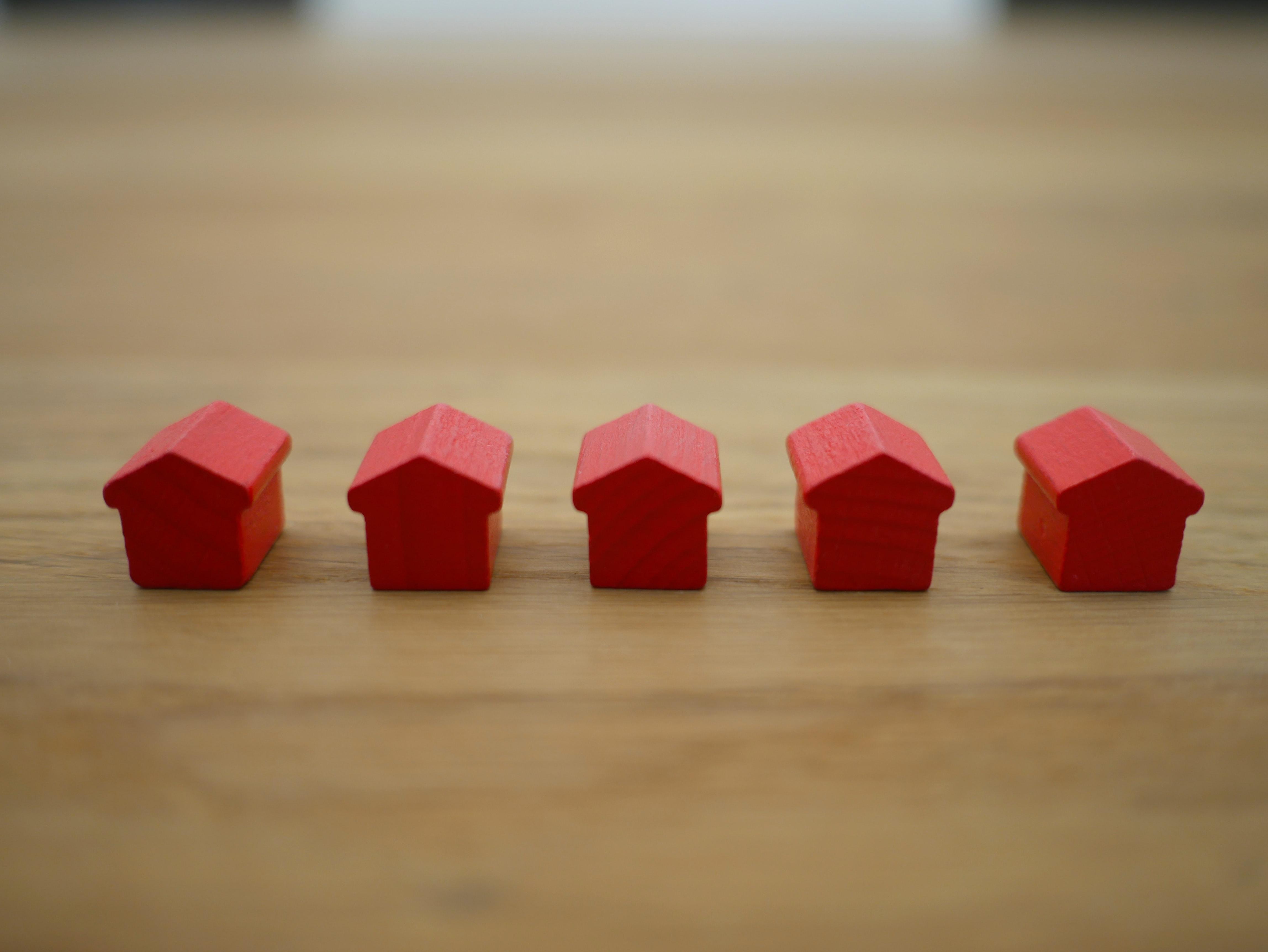 On voit sur cette photo cinq maisons de bois du jeu le monopoly
