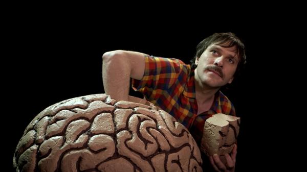 Homme qui plonge sa main dans un cerveau géant