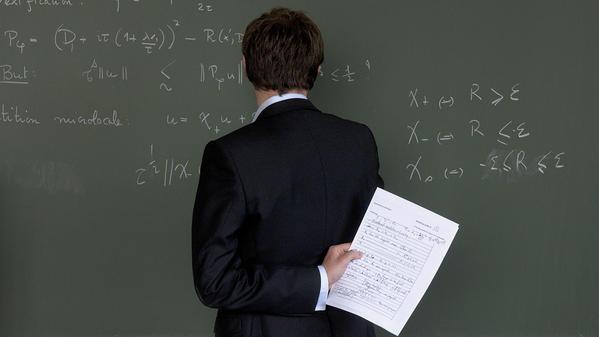 Homme face à un tableau vert sur lequel sont inscrit des équations.