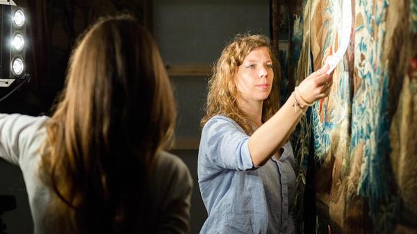 Deux chercheurs travaillent sur une tapisserie pour en étudier les couleurs
