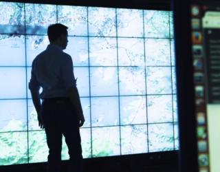 Homme en ombre chinoise devant mur d'écrans