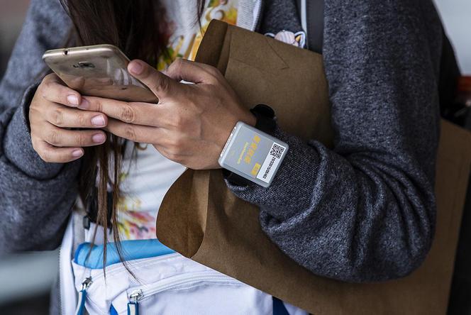 Un passager munis d'un bracelet électronique après avoir été testé au COVID-19 à l'aéroport de Hong Kong