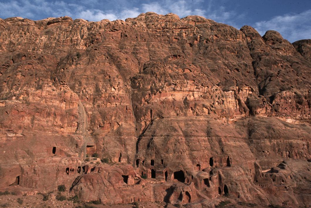 Chambres rupestres situées en bas d'une falaise du Jabal al-Khubtha