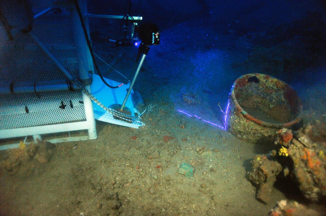 Sur le site d'une épave sous-marine, une machine scanne une jarre ensevelie avec un rayon lumineux violet.