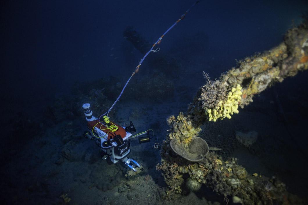 Le robot est au fond de l'eau. Au premier plan : l'ancre d'un bateau. On voit un câble qui part du robot.