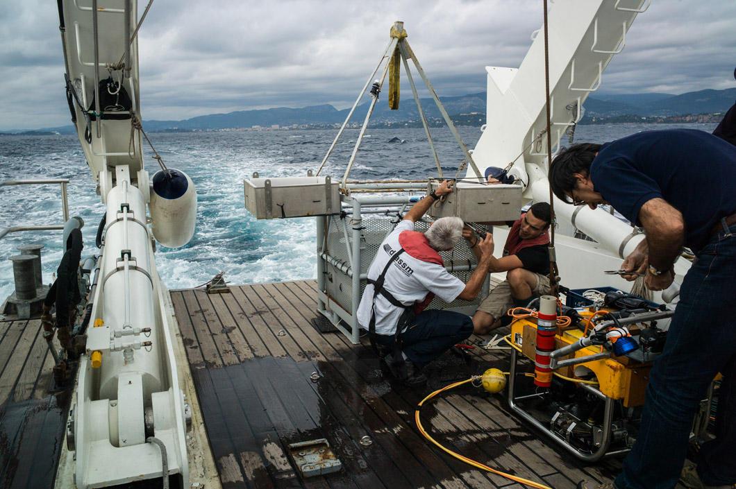 À l'arrière du bateau, des hommes manipulent des machines.