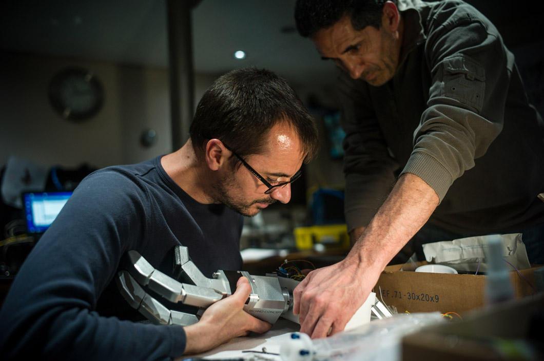 Un ingénieur manipule une main robotisée.