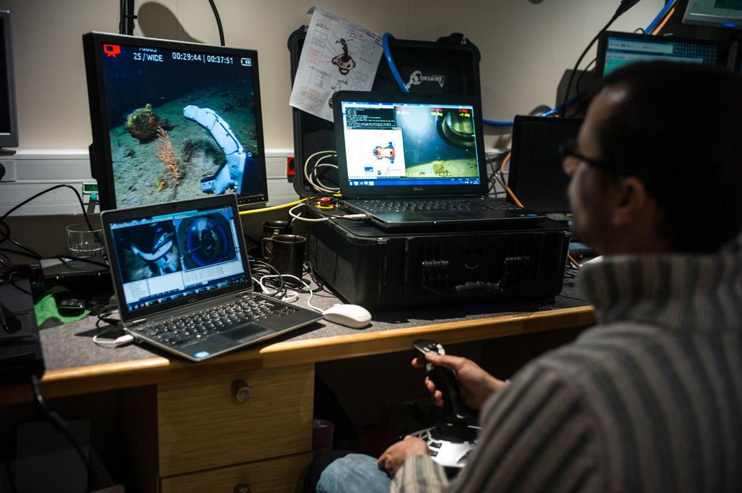 Un opérateur tient un joystick devant trois écrans d'ordinateur. Il est en train de piloter le robot.