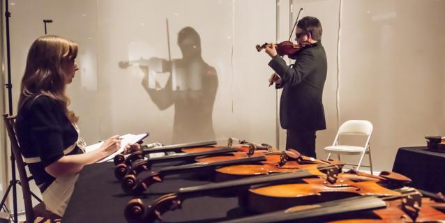 Le violoniste Aaron Boyd en train de tester des violons