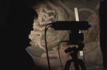 Chercheur et son instrument en ombre chinoise devant une peinture murale