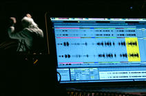 Un ordinateur en premier plan, derrière on voit un homme qui fait penser à un chef d'orchestre