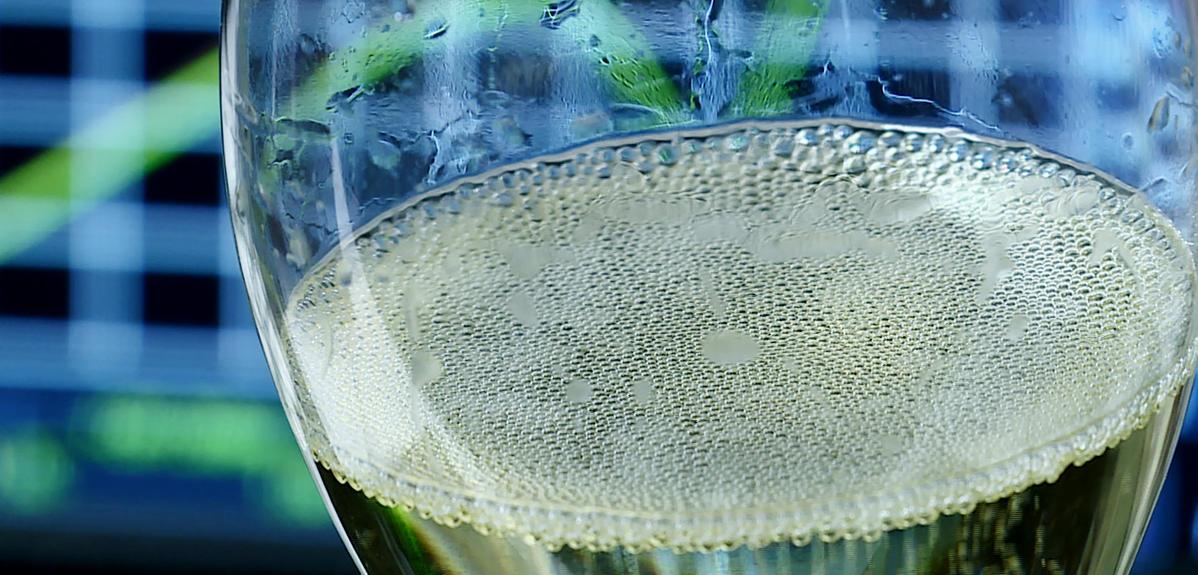 Bulles à la surface d'un verre de champagne placé devant l'écran d'un oscilloscope qui affiche des courbles