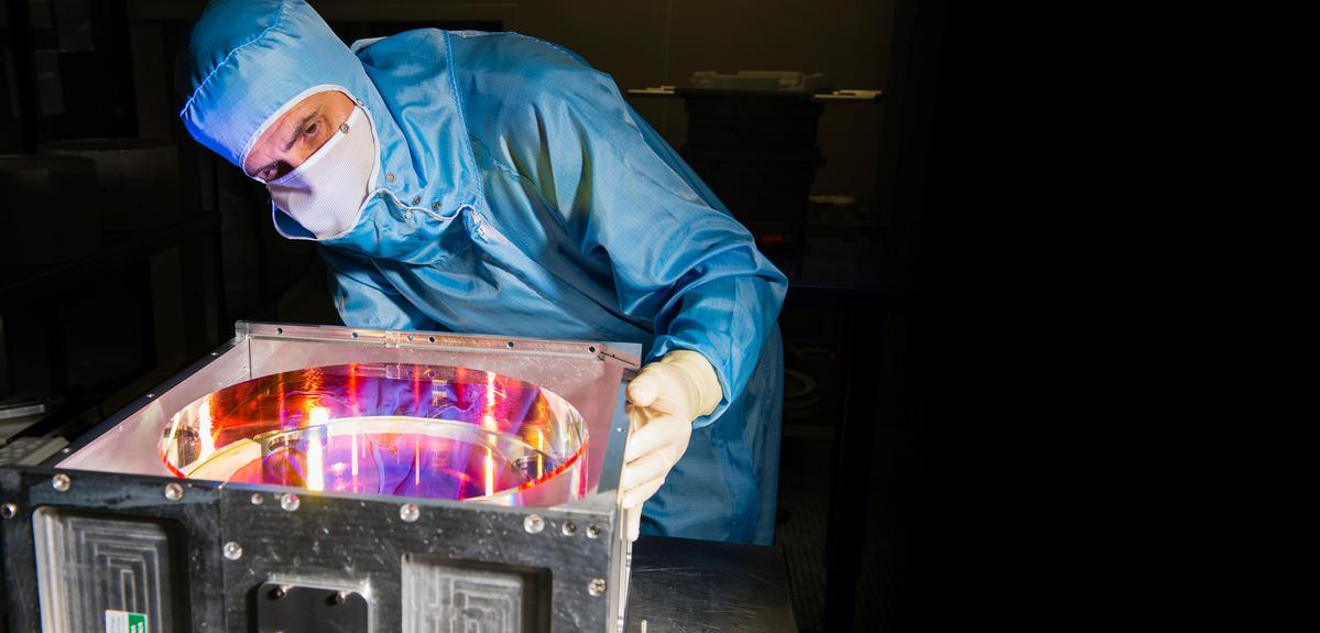 Ingénieur en train d'inspecter un miroir de couleur rosé