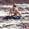 Deux personnes accroupies sur une plage jonchée de plastique.